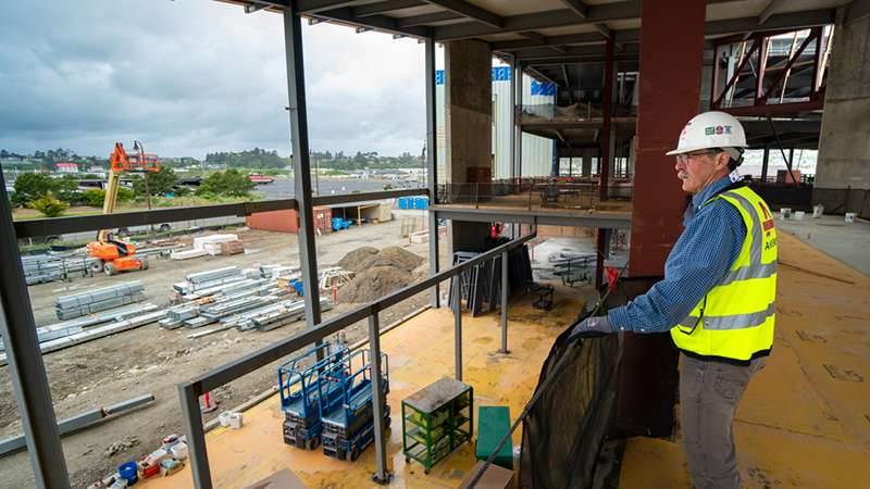 Bob Cowen stands inside of Marine Studies Building under construction. He is looking out at Hatfield campus.