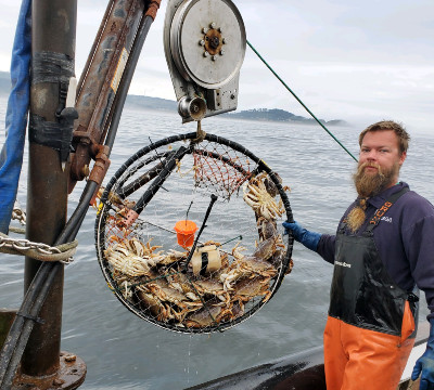 Dungeness crab fisherman Pat Kemmish with a crab pot mounted with an oxygen sensor.