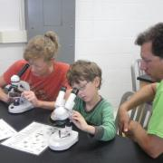 Family examining plankton with microscopes.