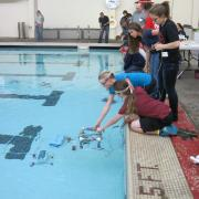 Competition team placing ROV into pool.