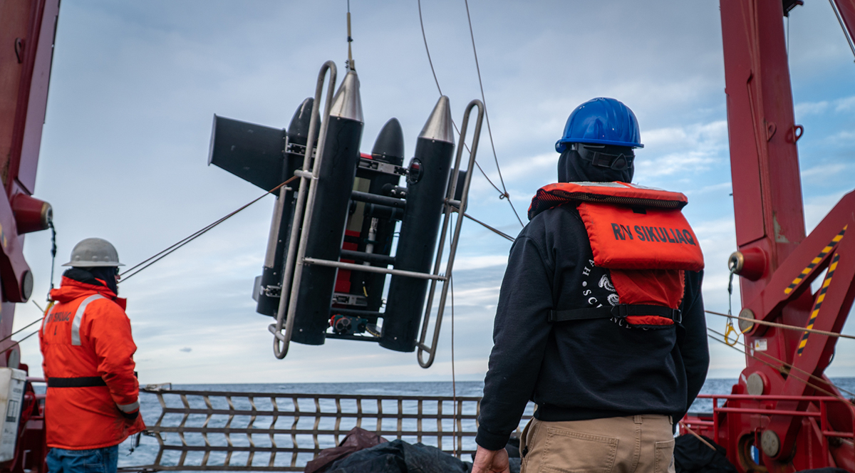 motorized deep water sampling equipment being lowered into the ocean off a boat