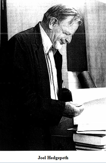 Joel Hedgepeth, an old white man with a beard, squints and leans over a stack of books. Black and white photograph, side-profile.