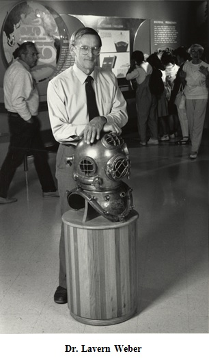 Lavern Weber, first HMSC director, stands in the old HMSC Visitors Center,his hands crossed over top of an antique scuba helmet on display.