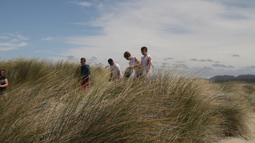 Students in dune grass at beach