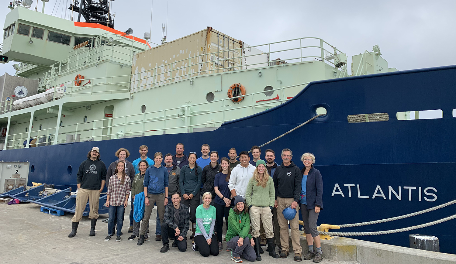 Research crew stands on dock with a large research vessel called the Atlantis behind them.