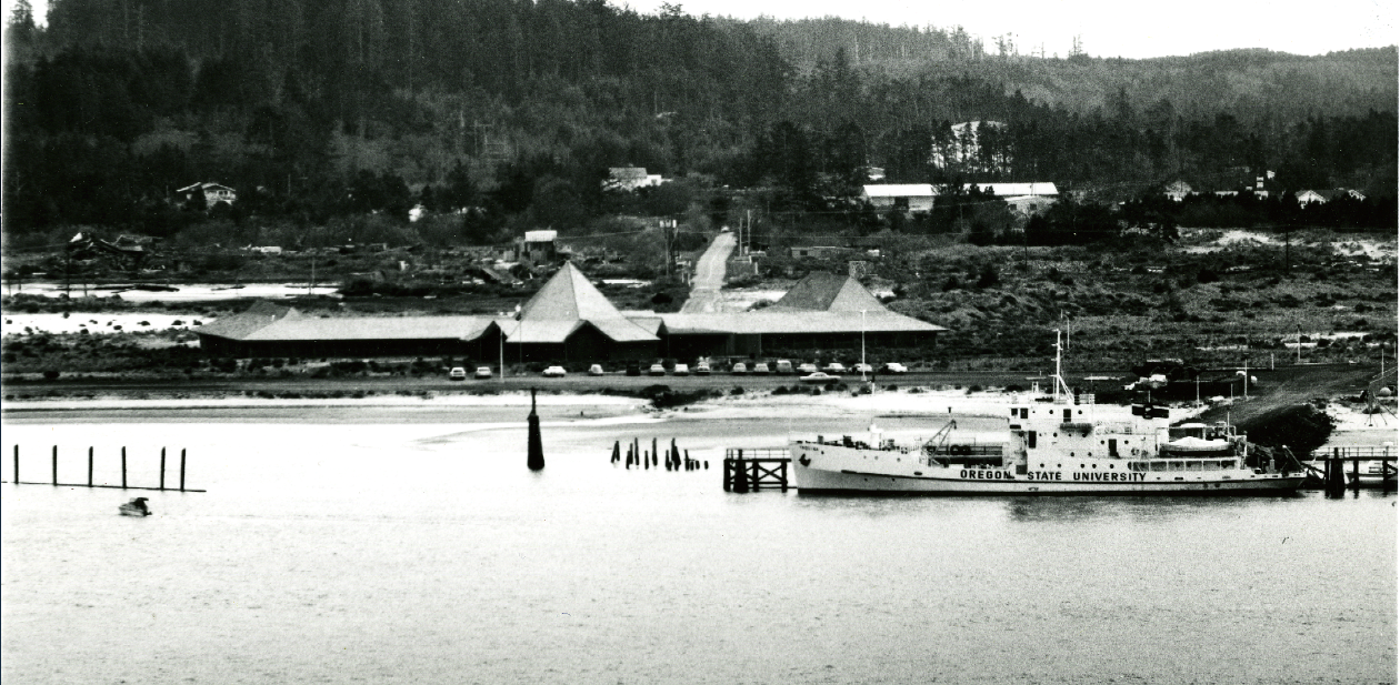 Black and white image of Marine Science Center from Yaquina Bay, facing South. Primary buildings shown, with forest in background. Research vessel Yaquina docked in front of center (foreground)