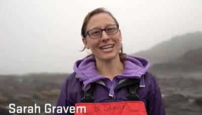 Researcher Sarah Gravem stands on a rocky tidal shore in outdoor gear.