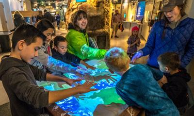 Families enjoy learning and playing in the augmented reality sandbox.