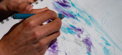 hands of an artist drawing a picture of the ocean waves
