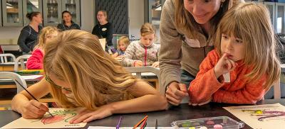 A mother helps her two young daughters with a painting and drawing activity