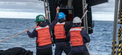 A research crew, wearing life vests and hard hats, hoists equipment onto a ship while out on stormy seas.
