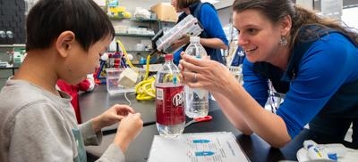 A young female teacher works with a young student in a science lab. She is pouring liquid into a container explaining the process to her student.