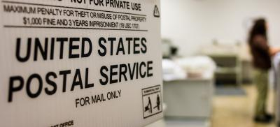 Foreground image of U.S. Postal Service Mail Only sign on the side of a box. In the background is a slightly blurred mailroom.