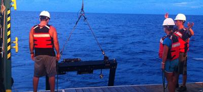 Graduate student researchers deploy sampling equipment off a boat.