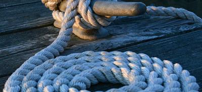 Rope coiled in a circle laying on the deck of a ship