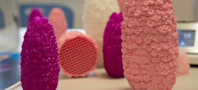 A group of 3D printed shapes stand on a table.