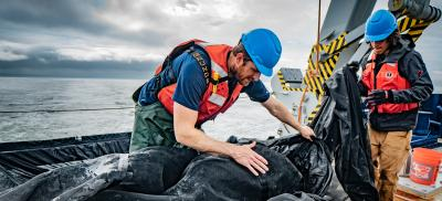 research graduate students work on sampling equipment on a boat at sea